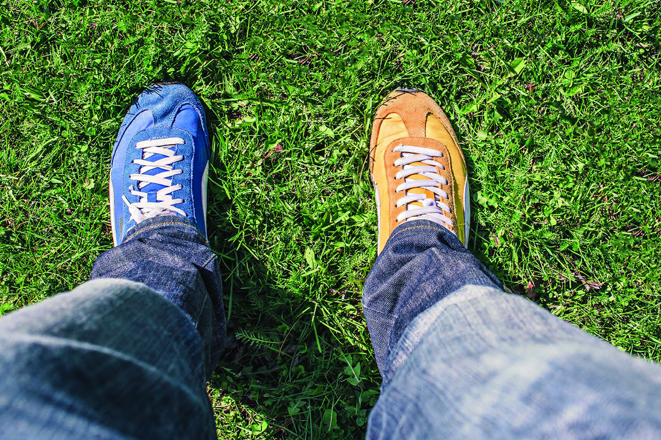 looking down as shoes standing on grass