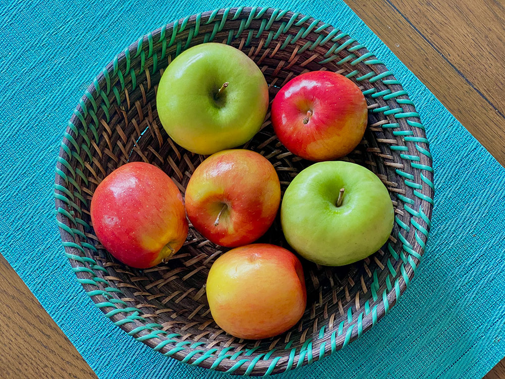 Image of red and green apples in a bowl on a blue table runner